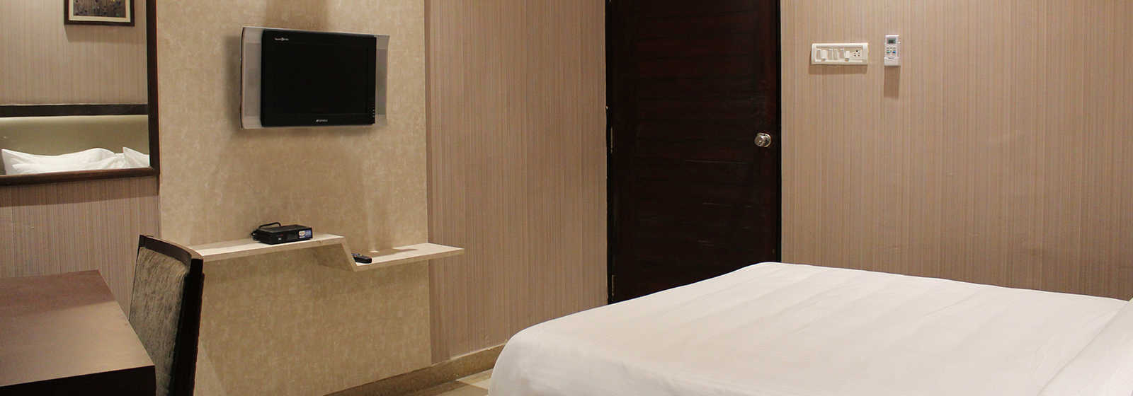 Super Deluxe room equipped with TV and study table at The Byke Signature, a business hotel in Bangalore.